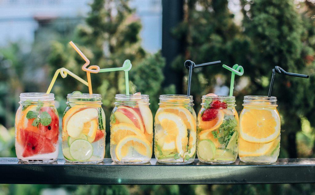 Drinks com frutas variadas e canudos divertidos enfileirados em corrimão. Ao fundo paisagem com árvores verdes