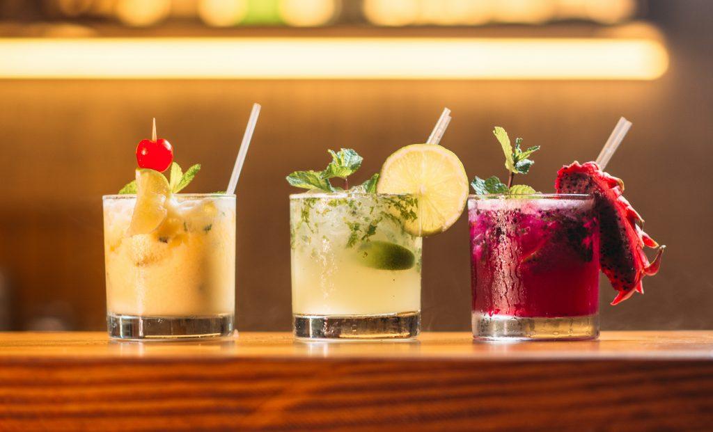 Três caipirinhas coloridas com copos decorados com frutas sobre balcão de bar.