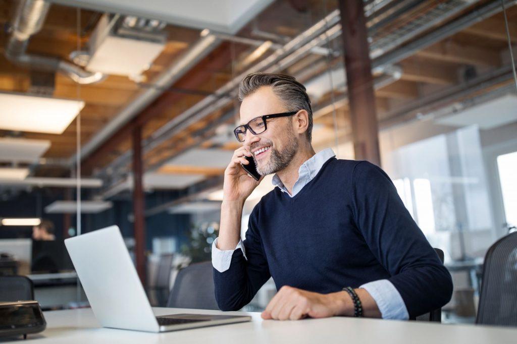 Homem de óculos sorri e segura celular na orelha. Ele está sentado no escritório olhando para a tela de um notebook aberto.