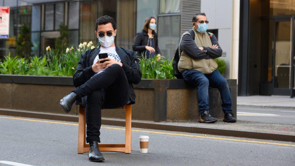 Homem usando máscara e óculos escuros em um banquinho no meio da rua próximos de outras pessoas que também usam máscara.