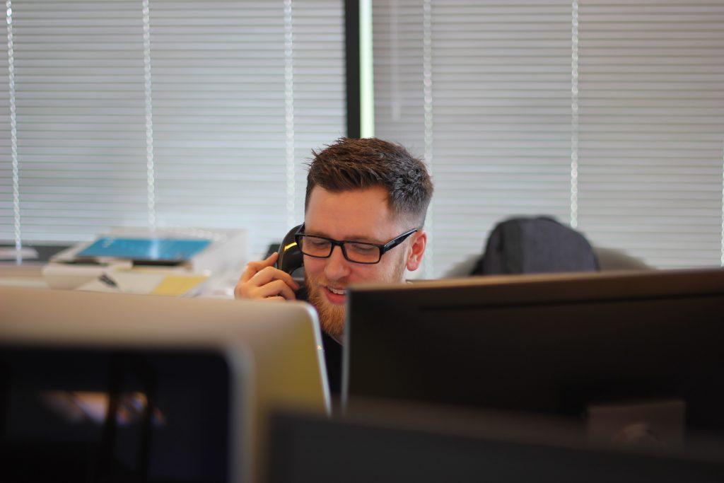 Homem de óculos falando no telefone atrás de dois monitores de computador. Ao fundo, janelas com persianas.