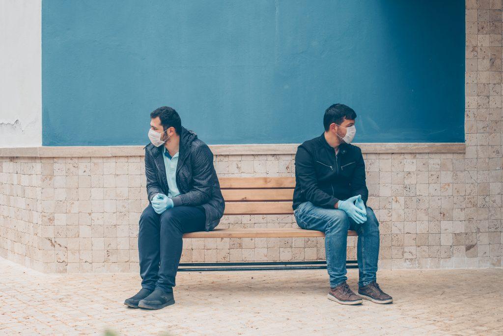 Dois homens de máscara e luvas sentados em um banco de madeira. Eles estão distantes um do outro. Ao fundo parede azul.