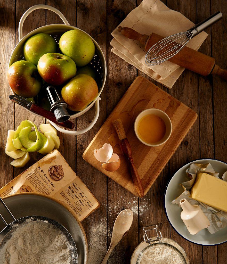 Vários ingredientes em cima de uma mesa de madeira. Há maçãs, ovos, farinha e manteiga, além de utensílios da cozinha.