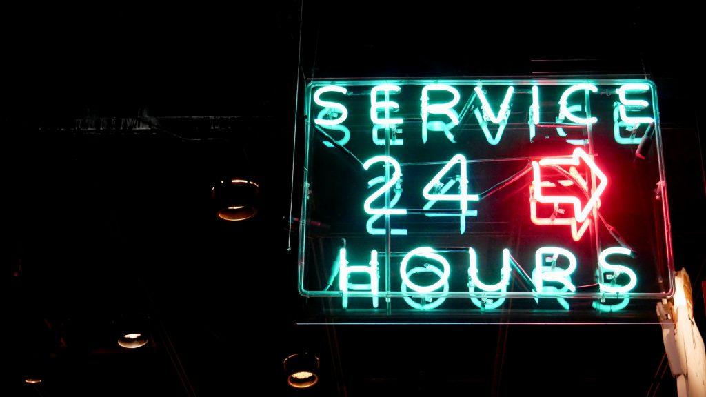 """Luminoso com os dizeres """"aberto 24 horas"""" em inglês, e uma seta para o lado direito."""