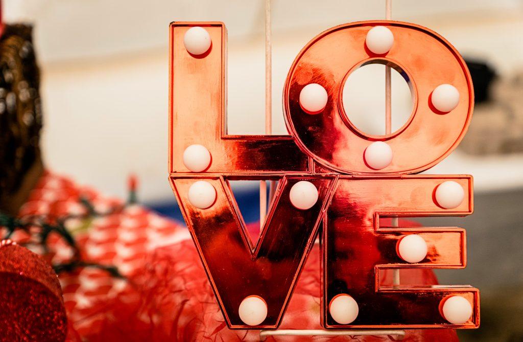 Letreiro luminoso em vermelho formando a palavra LOVE. Há lâmpadas em cada uma das letras que formam a palavra.