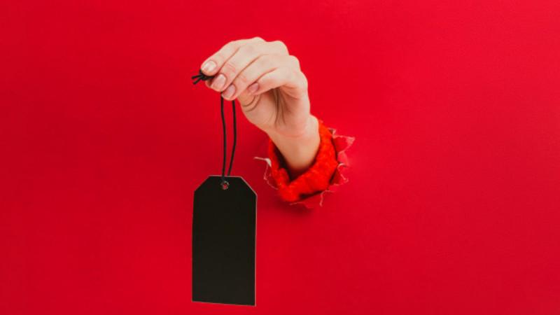 Em fundo vermelho, uma etiqueta de preço preta é segurada por uma mão que sai da parede.