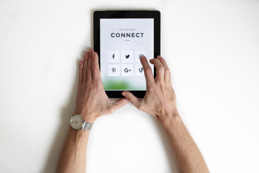 Mãos de uma pessoa sobre superfície branca segurando tablet e clicando nos ícones das mídias sociais