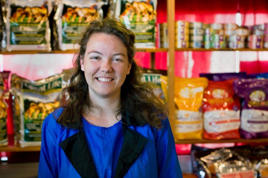 Mulher com um uniforme azul sorri na frente de prateleira com sacos de ração de embalagens coloridas.