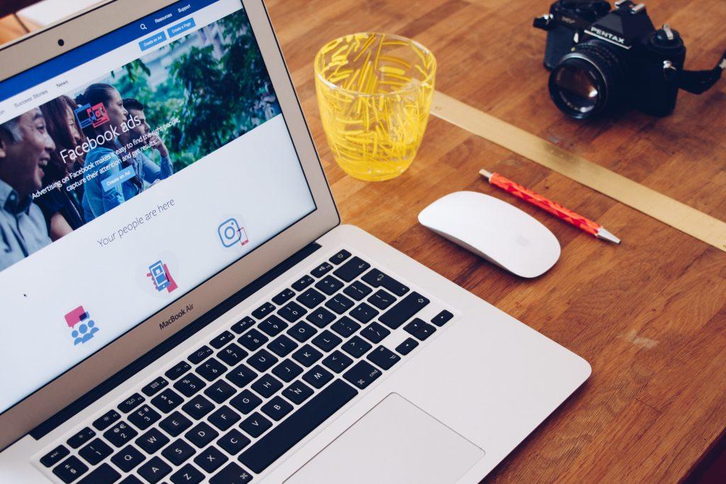 Notebook aberto na página do Facebook Ads. Ao lado há mouse branco, caneta laranja, copo amarelo e câmera fotográfica