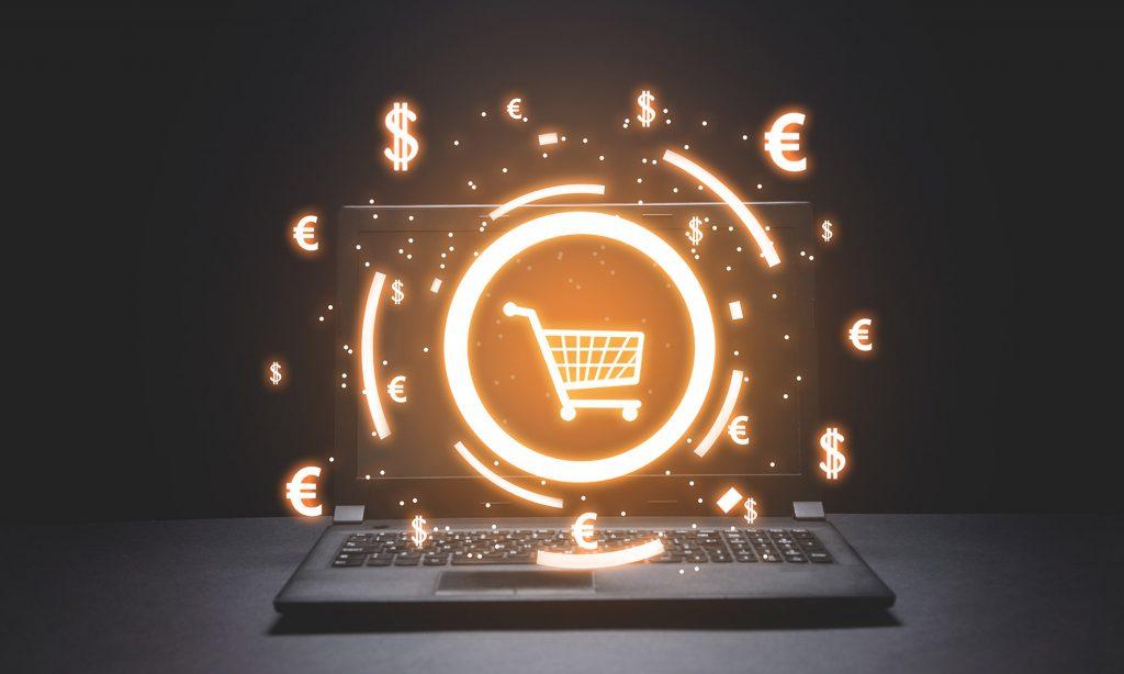 Sobre um fundo preto, um notebook aberto mostra ilustração neon de carrinho de supermercado e símbolos de dólar e euro.