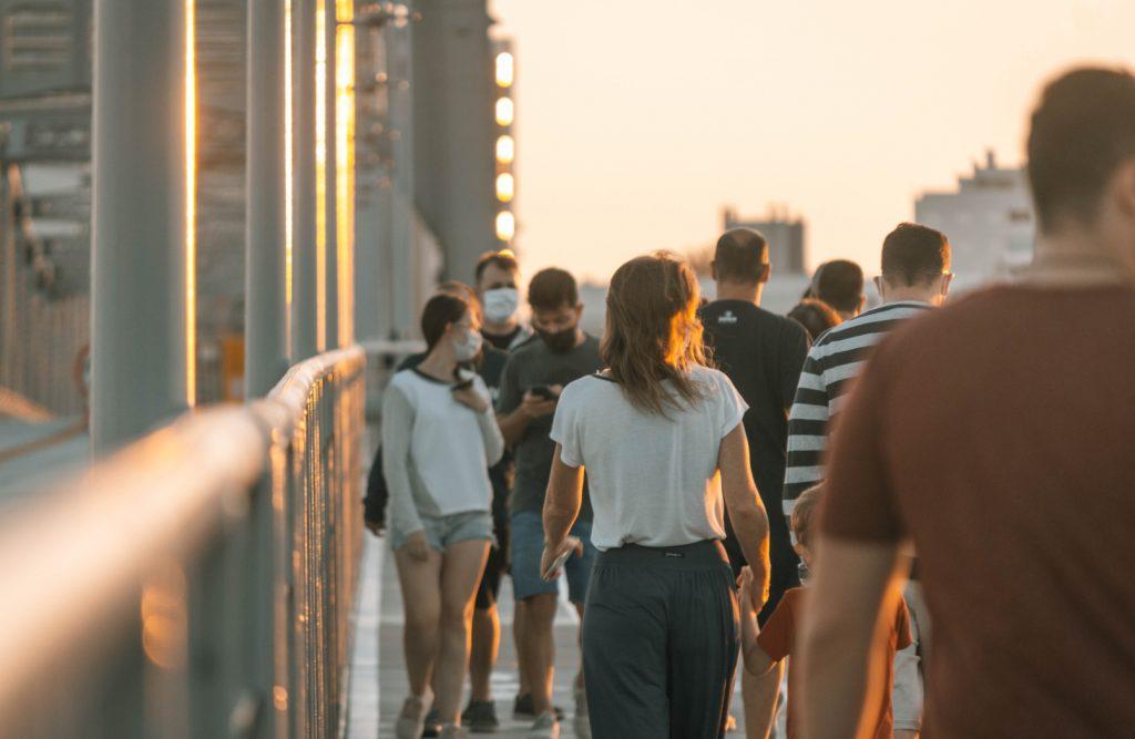 Pessoas com máscaras andando em calçada.