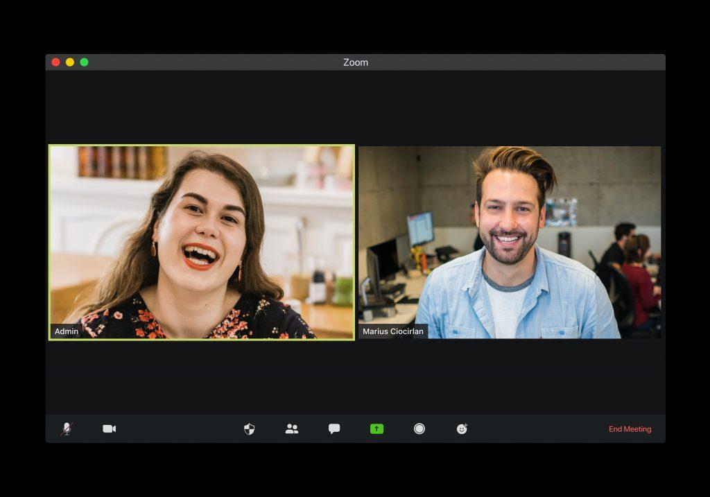 Homem e mulher sorrindo na interface de um programa de videochamada. O homem está num escritório, e a mulher, em casa.