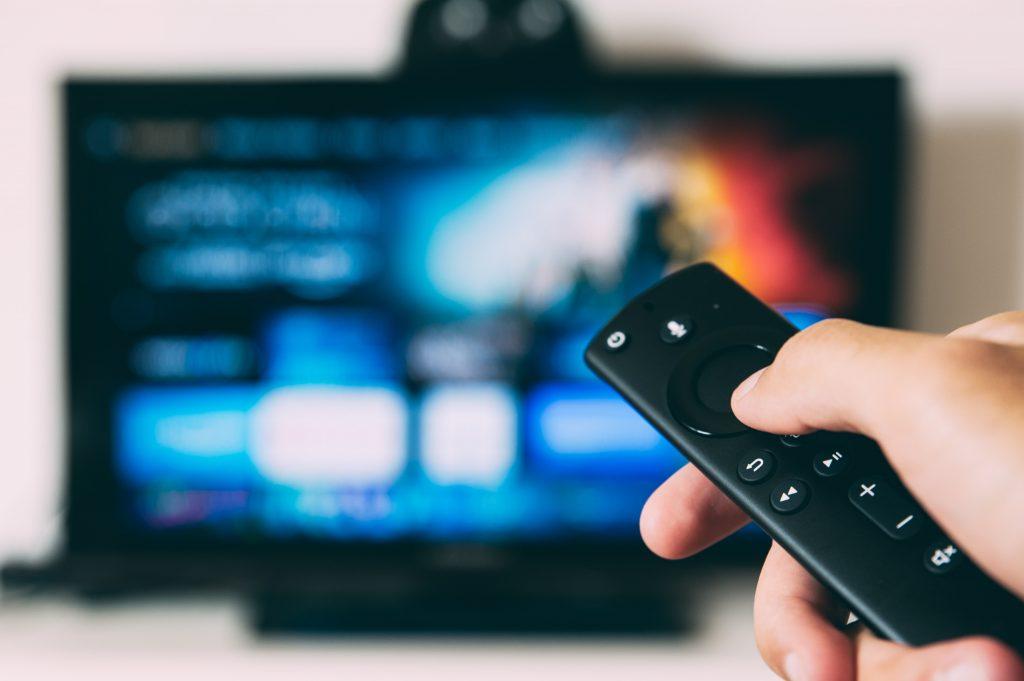 Em primeiro plano, uma pessoa apertando botão de controle remoto, ao fundo uma Smart TV preta.