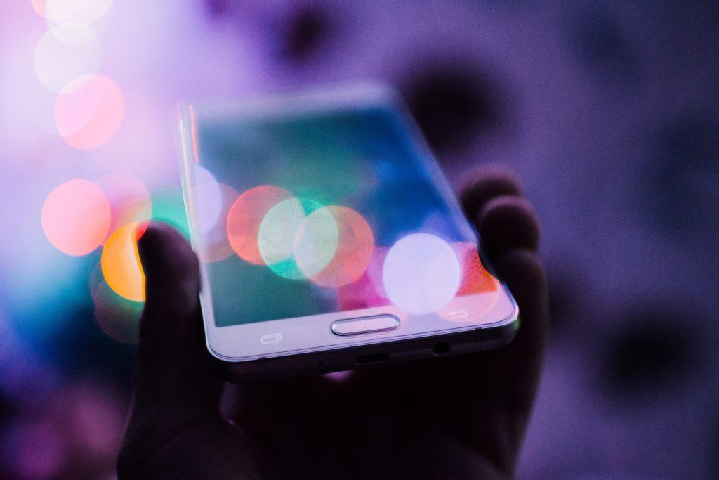 Uma mão segurando um smartphone branco. A imagem é composta pelo reflexo de luzes da cidade sob o aparelho.