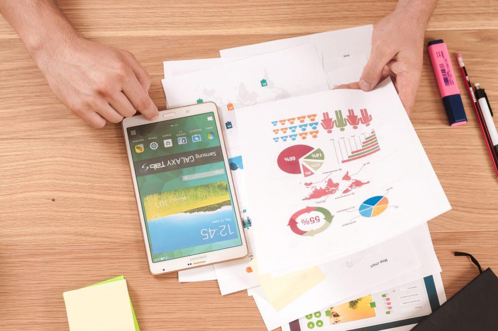 Mãos de uma pessoa sobre mesa segurando smartphone e folhas de papel com gráficos coloridos. Ao lado há canetas coloridas.