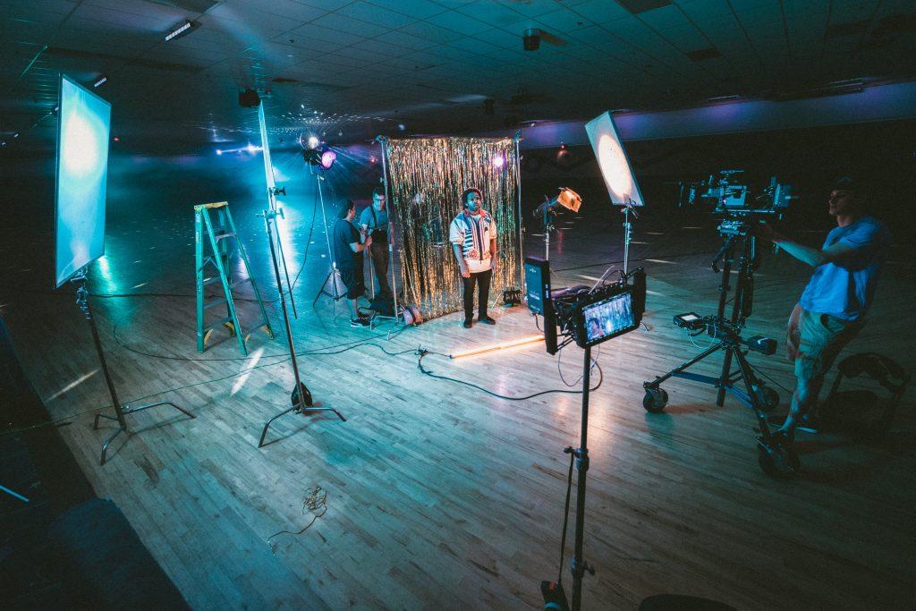 Studio de filmagem com câmeras nos tripés, refletores, luzes e uma pessoa em pé próxima de uma cortina.