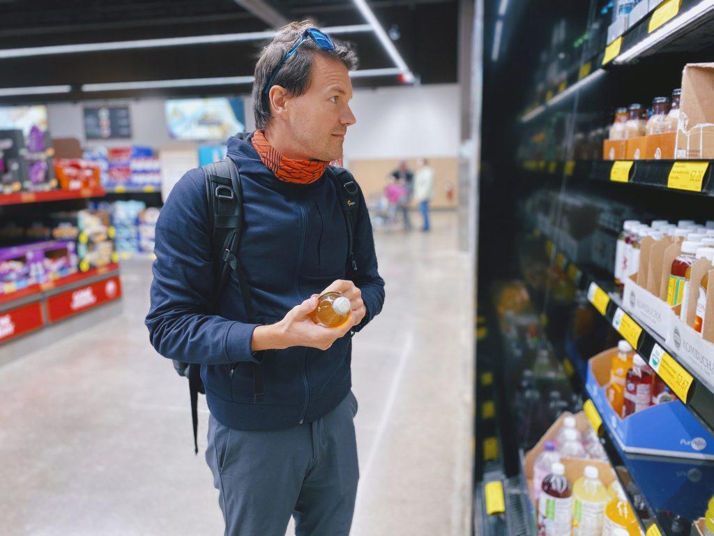 Homem de roupas de frio em um supermercado. Ele segura uma garrafa nas mãos enquanto observa as outras em um refrigerador.