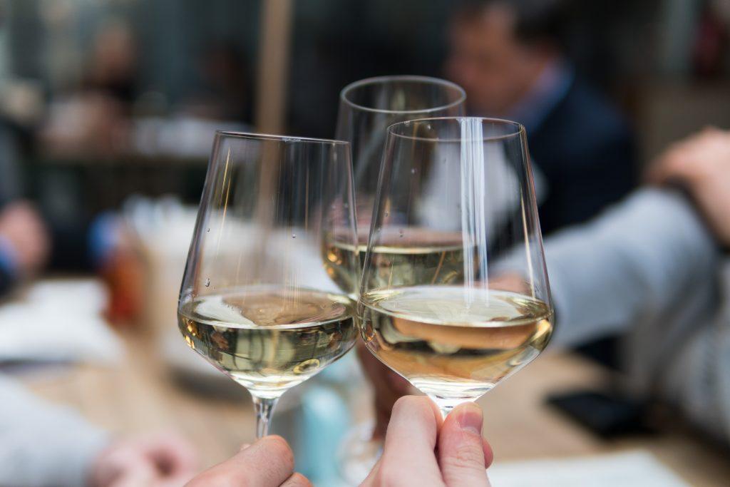 Três taças com vinho branco seguradas e sendo brindadas por três pessoas.