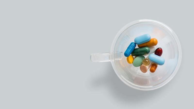 Xícara de plástico com cápsulas de vitaminas coloridas.