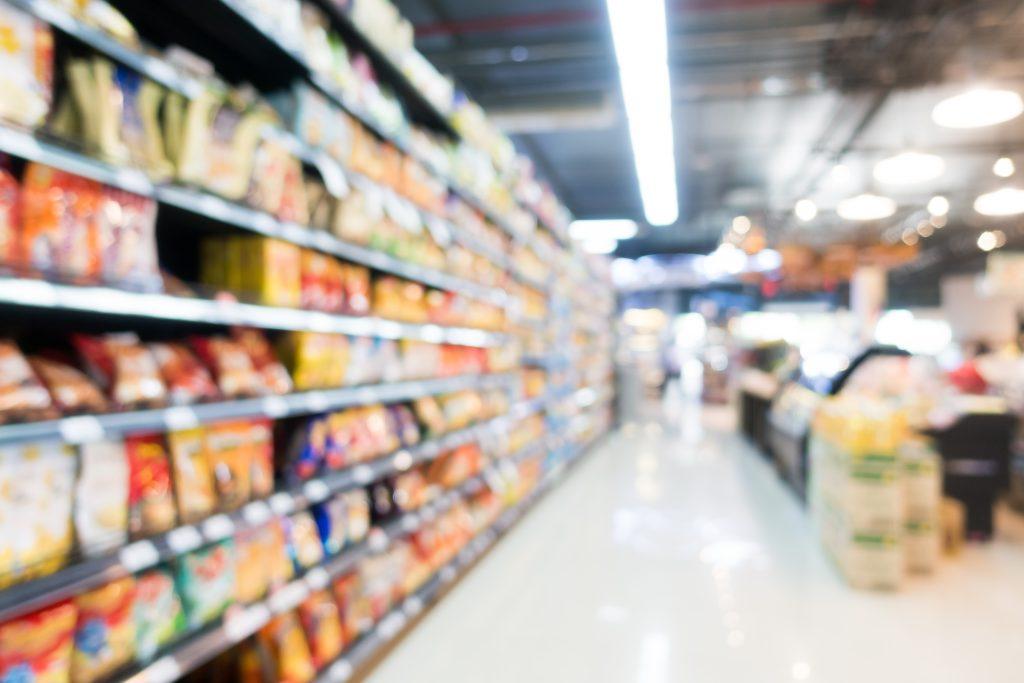 Corredor com prateleiras de um supermercado com luz branca.