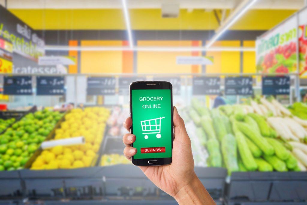 Mão de uma pessoa segura smartphone com ícone de supermercado delivery na tela. Há caixotes de verduras de sacolão ao fundo.
