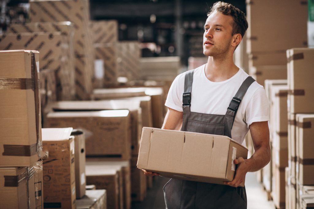Carregador de estoque com caixa na mão procurando espaço no depósito.