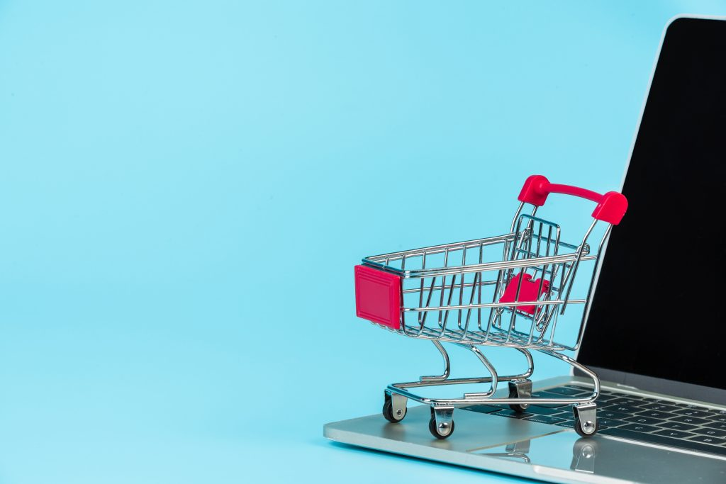 Em um fundo azul, carrinho de compras em miniatura em cima de computador.