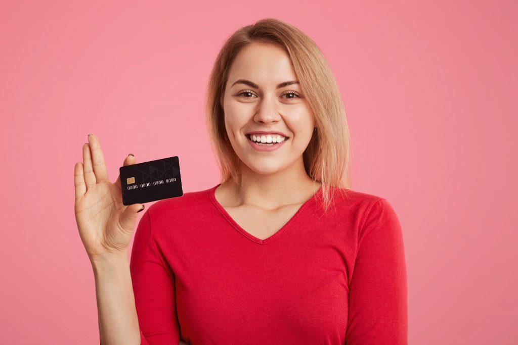 Em um fundo rosa, uma mulher loira segura um cartão de crédito preto.