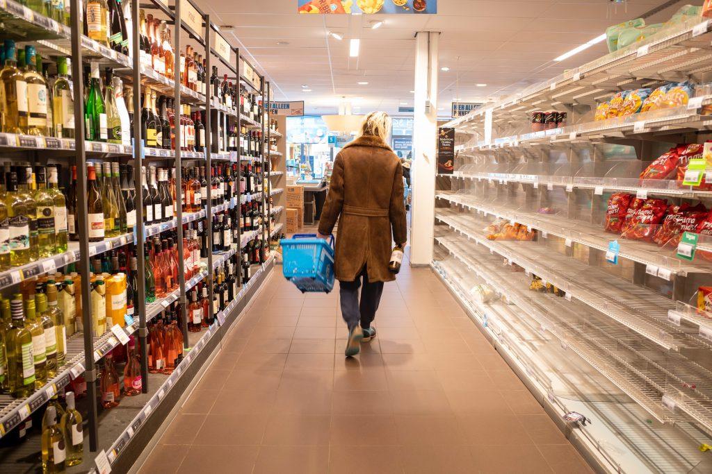 Uma pessoa de costas segurando cesta de compras andando em corredor com algumas prateleiras de supermercado vazias