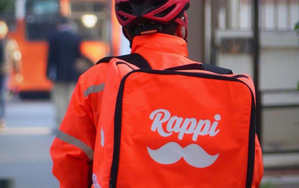 Homem de costas usando capacete, roupa laranja e mochila de entregador do Rappi.