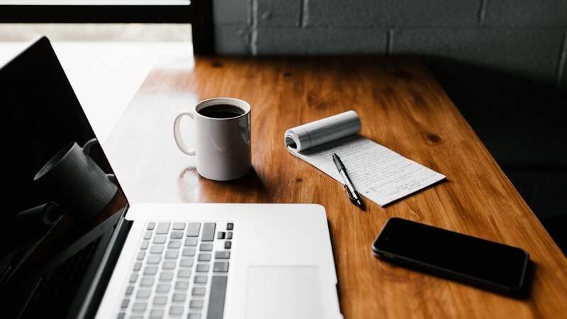Notebook aberto com a tela desligada, smartphone preto, caneca branca cheia de café e bloco de anotações em mesa de madeira.