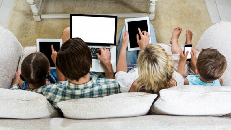 Família sentada no sofá com aparelhos eletrônicos nas mãos: tablet, smartphone e notebook.