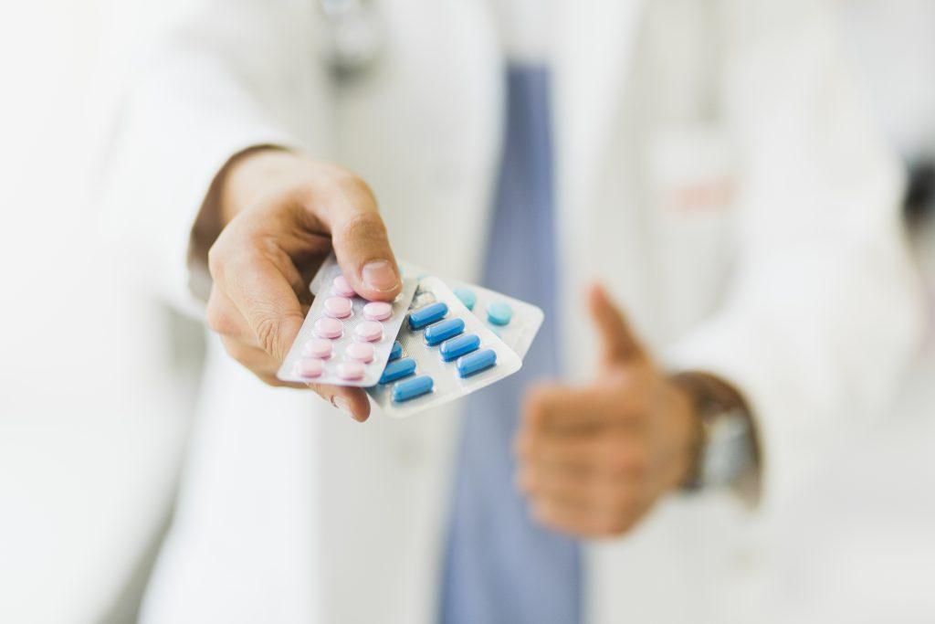 Em primeiro plano, mão humana entregando três cartelas de remédios de cores diferentes.