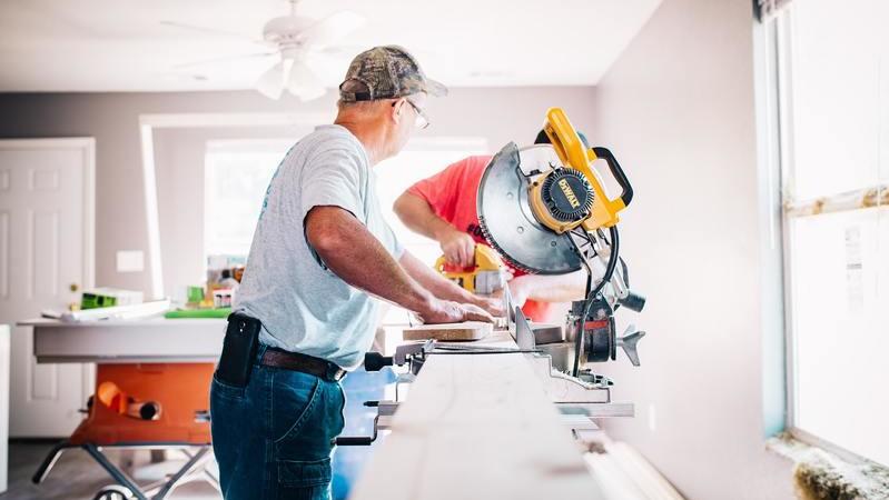 Homem de boné com as mãos apoiadas sobre superfície de madeira próximo de uma máquina de corte.