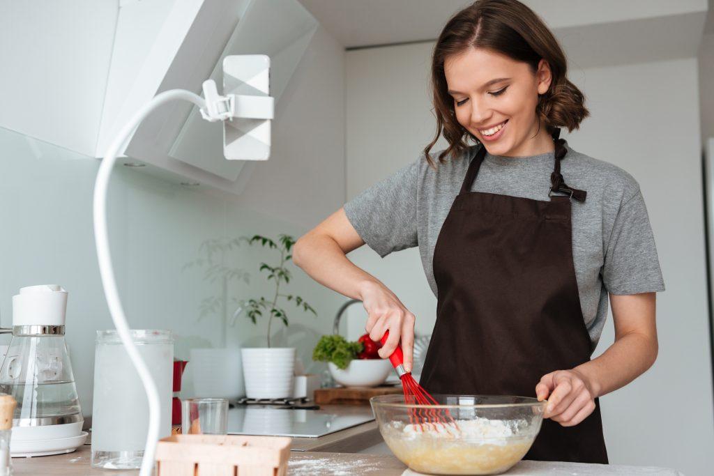 Uma mulher na cozinha, mexendo uma vasilha de vidro. Ela também está gravando a receita com um celular.