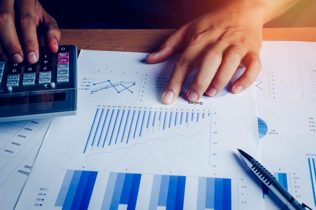 Mãos de uma pessoa repousada sobre um relatório com gráficos e usando a calculadora.
