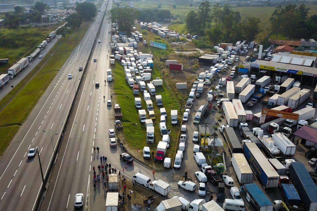 Caminhões estacionados à beira da estrada, em posto, e estrada vazia.