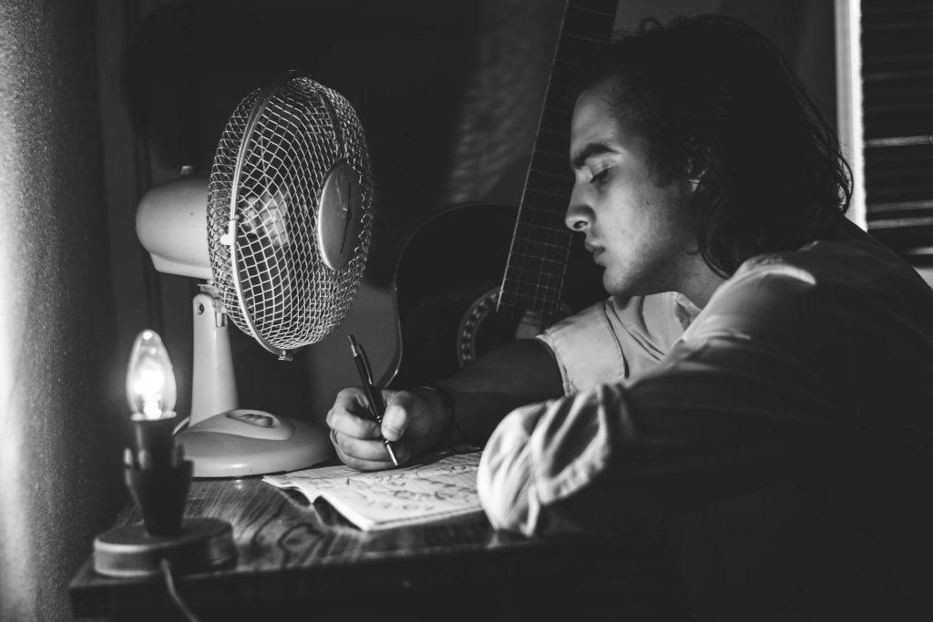 Imagem em preto e branco de um homem sentado à mesa escrevendo em caderno de frente para um ventilador e próximo a violão.