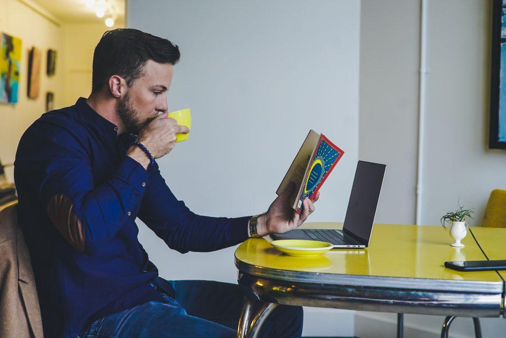 Homem sentado segurando xícara amarela e segurando um livro na outra mão. Na frente um computador.