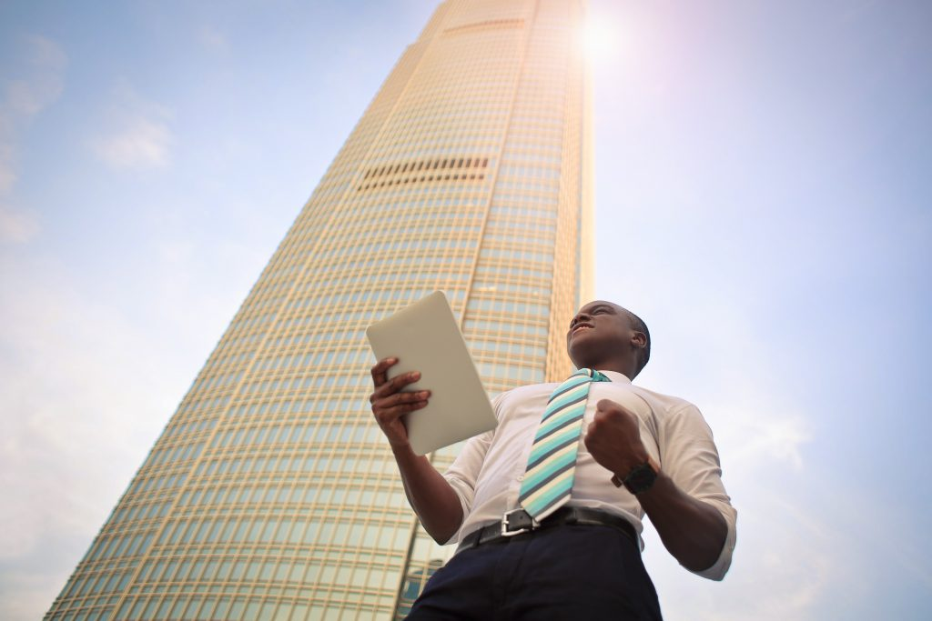 Homem segurando tablet de pé ao lado de um prédio alto. Ele faz gesto de vitória com a mão