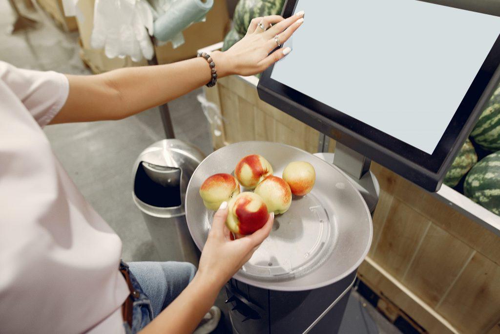 Mão de uma mulher finalizando compras via computador, exemplificando o varejo sem toque na pandemia de 2020.