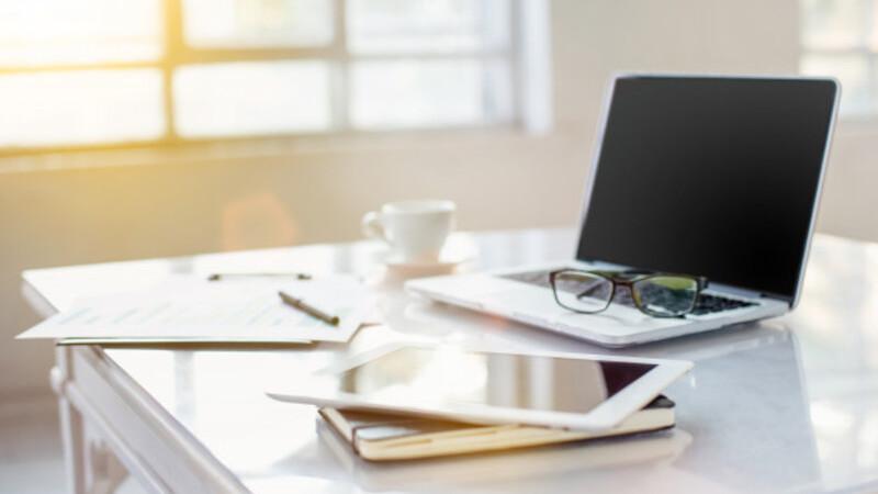 Imagem mostrando um notebook, papel, agenda e uma xícara de café em um fundo branco.