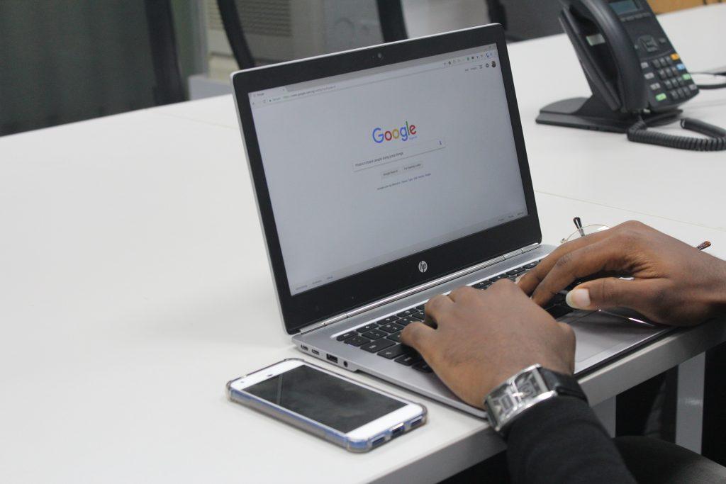 Mãos de uma pessoa sobre teclado de notebook ligado com a interface do Google na tela.