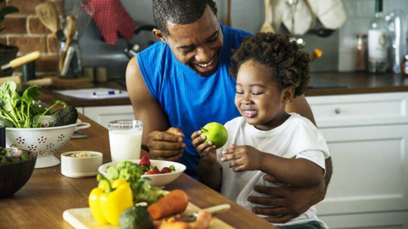 Pai e filho em uma cozinha, com frutas e legumes sob uma mesa de madeira