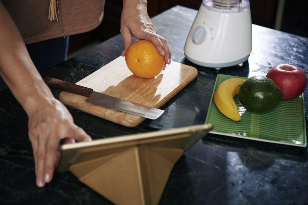 Mesa com uma laranja, banana, abacate, tábua e faca para cortar as frutas. Ao fundo um liquidificador.