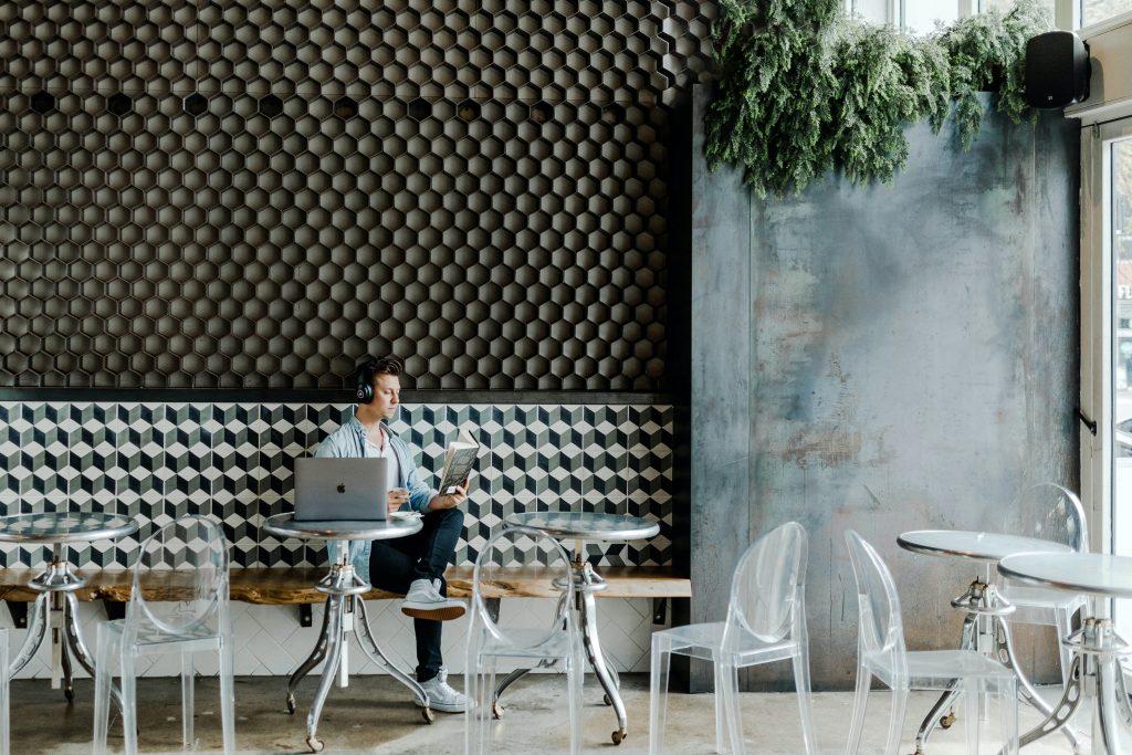 Homem sentado usando fones de ouvido e lendo um livro. Ele está em um restaurante com várias mesas e cadeiras vazias.