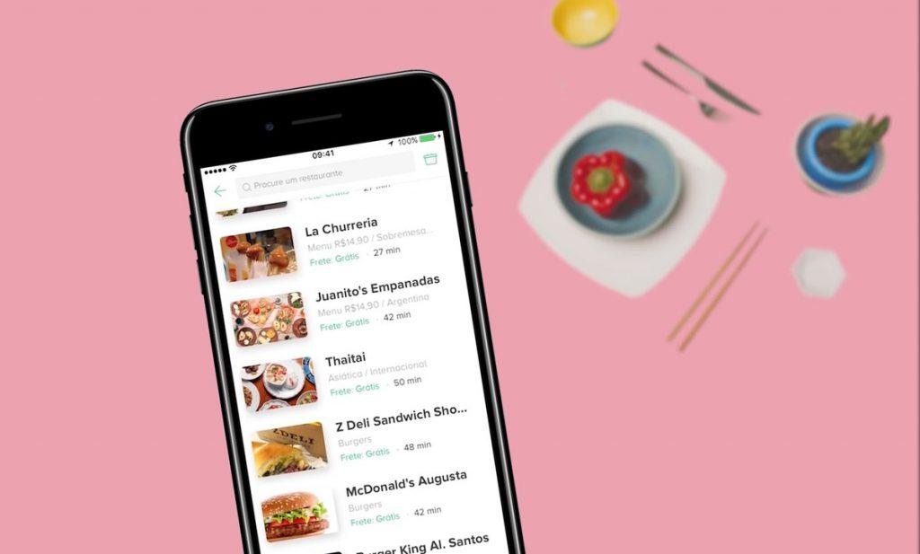 Smartphone na interface do Rappi mostra várias opções de restaurante. O fundo de cor de rosa com a mesa posta para refeição.
