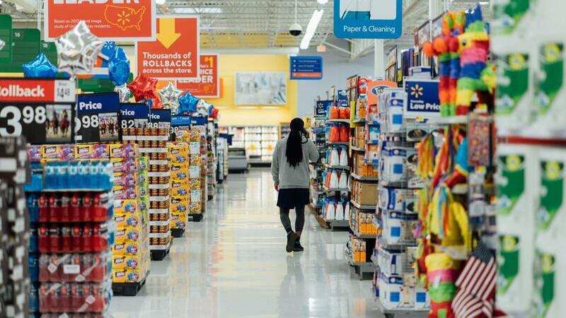 Pessoa andando entre gôndolas de supermercado vazio.
