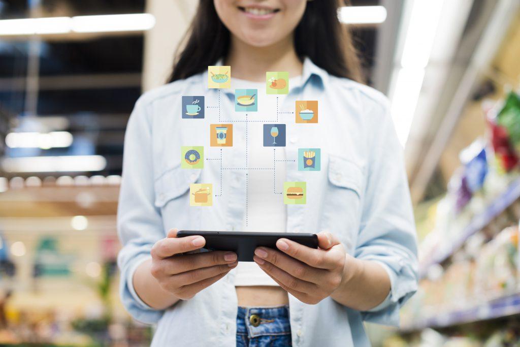 Mulher em loja física segurando um tablet com ícones acima da tela