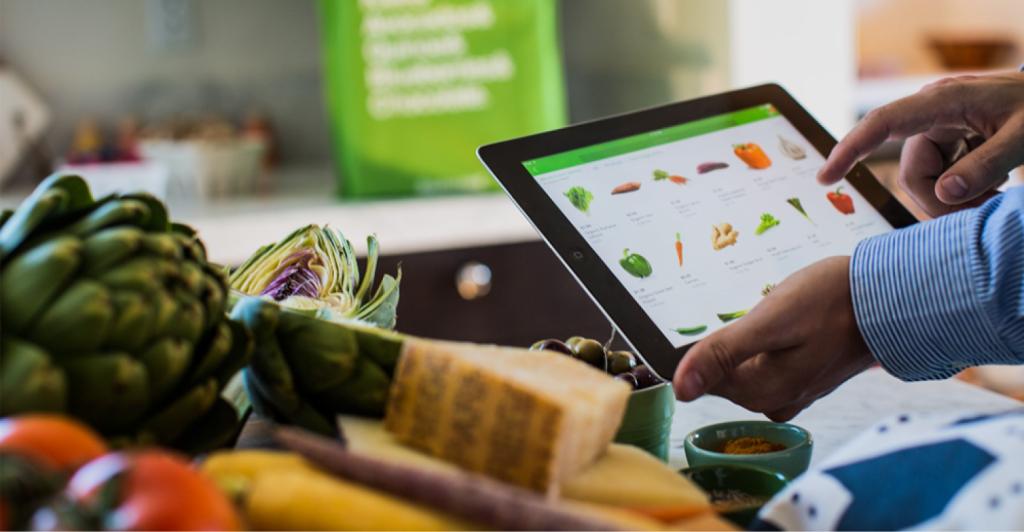 Uma pessoa segurando tablet com interface de supermercado online próximo de algumas verduras sobre a mesa.